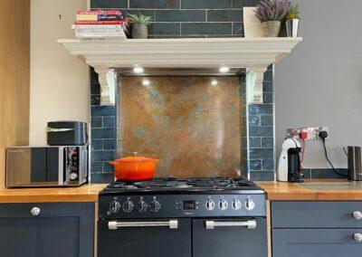 aged copper kitchen backsplash next to grey tiles