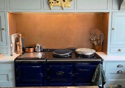 copper splashback behind aga in kitchen