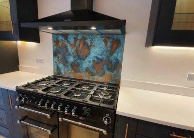 verdigris aged copper splashback behind kitchen hob